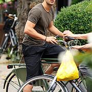 NLD/Amsterdam/20150702 - Voetballer Evgeniy Levchenko op de fiets in Amsterdam