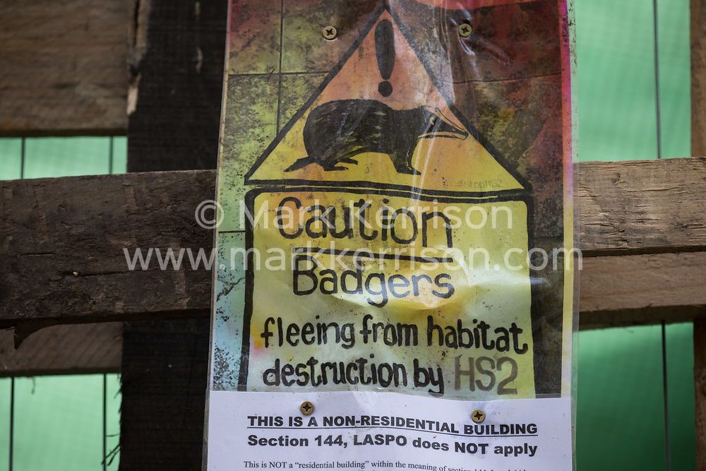Wendover, UK. 20th February, 2021. A sign warning of the threat posed to badgers by the HS2 high-speed rail link is pictured at the Wendover Active Resistance Camp which is occupied by activists from HS2 Rebellion. A chain of such camps has been built by environmental activists along the planned route of the rail project from Euston in London to Birmingham.