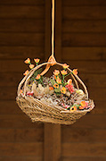 flower arrangement in straw basket hanging from a orange string