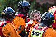 Hampshire Police officers remove Dan Hooper, widely known as Swampy during the 1990s, from the river Colne for arrest on 8th December 2020 in Denham, United Kingdom. The climate and roads activist had occupied a bamboo tripod positioned in the river the previous day in order to delay the building of a bridge as part of works for the controversial HS2 high-speed rail link and a large security operation involving officers from at least three police forces, the National Eviction Team and HS2 security guards was put in place to facilitate his removal.