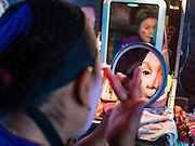 08 DECEMBER 2016 - BANGKOK, THAILAND: A woman puts on her makeup before a Chinese opera (also called ngiew in Thailand) performance at Pek Leng Keng Shrine in the Khlong Toei neighborhood of Bangkok. Public performances of music and celebration were banned during the first 30 days of the mourning period for Bhumibol Adulyadej, the Late King of Thailand. Now, nearly two months after the revered monarch's death, Bangkok street life is returning to normal and Chinese temples and shrines are once again scheduling operas.      PHOTO BY JACK KURTZ