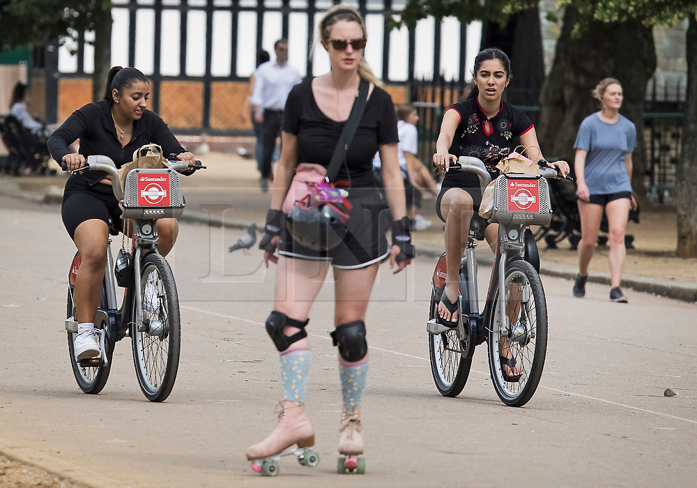 © Licensed to London News Pictures. 09/07/2021. Two cyclists in Hyde Park, central London on a summer's day. Wet and warm conditions are expected over the weekend. Photo credit: Ben Cawthra/LNP