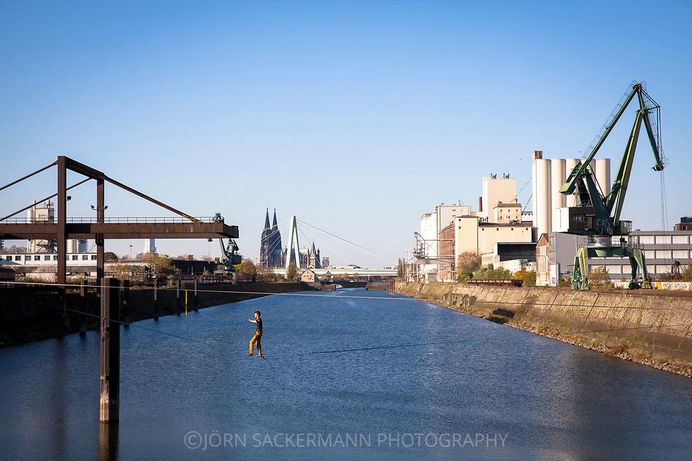 man on a slackline in the Rhine harbor in the district Deutz, in the background the cathedral and Severins bridge, Cologne, Germany.<br /> <br /> Mann auf einer Slackline im Deutzer Hafen am Rhein, im Hintergrund der Dom und Severinsbruecke, Koeln, Deutschland.