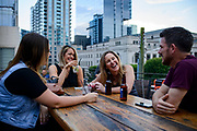 NASHVILLE, Tenn. - JUNE, 16: Micaela Arseneau, 31, from left, Carly Kremkau, 32, Laura Ames, 33, and Austin Arseneau, 32, all of Nashville, share a laugh while having a drink on the rooftop of FGL House in downtown Nashville on Saturday June 16, 2018. (Photo by William DeShazer/For The Washington Post)