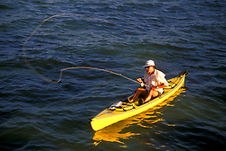 Stock photo of a man casting his fly fishing rod from his yellow kayak