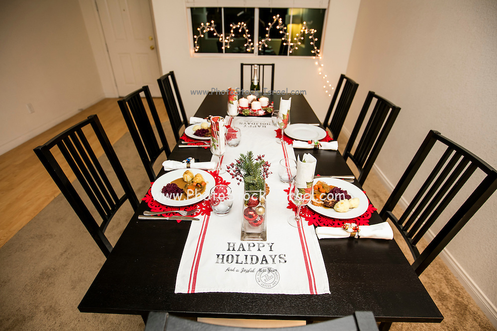 Christmas dinner table set and decorated with red and green