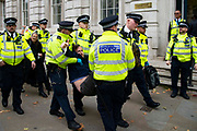 A man gives a thumps up as he is arrested in Whitehall on 7th October, 2019 in London, Untited Kingdom. Extinction Rebellion plan to occupy 12 sites situated around key Government locations around Westminster for two weeks to protest against climate change.