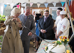 The Prince of Wales and Duchess of Cornwall cut a cake as they arrive at Newquay Fire Station, Cornwall, to meet residents from Tregunnel Hill, a mixed-use neighbourhood built on Duchy of Cornwall land in Newquay comprising open-market and affordable homes.
