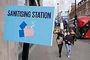Hand sanitising station as most shops now open but with retail sales suffering due to the Coronavirus pandemic, shoppers wearing face maks, which will become compulsory in shops on the 24th July, still come to Oxford Street, Londons main shopping district on 16th July 2020 in London, United Kingdom. Coronavirus or Covid-19 is a respiratory illness that has not previously been seen in humans. While much or Europe has been placed into lockdown, the UK government has put in place more stringent rules as part of their long term strategy, and in particular social distancing.