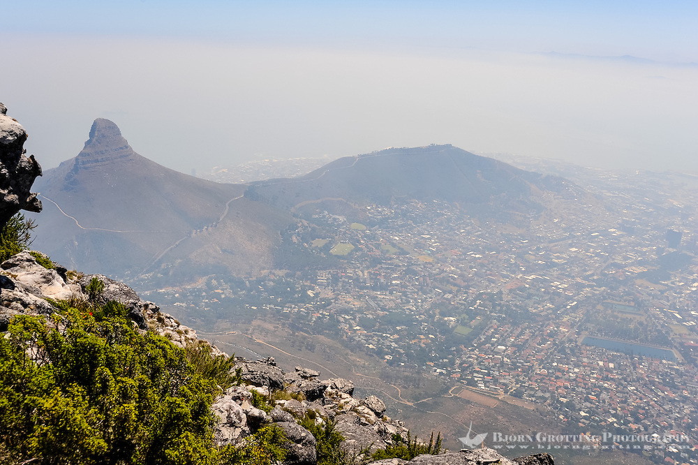 Table Mountain is a flat mesa  overlooking the city of Cape Town in South Africa. Lion's Head and Signal Hill to the west.