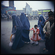Afghan women in burqa and a little girl with a red dress walk past a group of day laborers near the Kot-e-Sangi square in Kabul, Afghanistan, Sunday, Nov. 5, 2006.