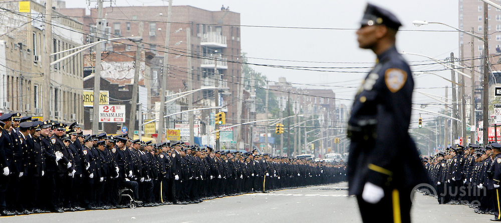 Police officers line a street during the funeral for a New York City police officer in Brooklyn, New York.