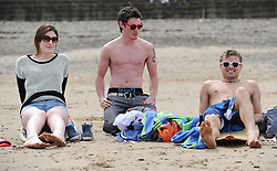 © Licensed to London News Pictures. 27/05/2013..Saltburn, England..From left Christina Muller, Sean Kelly and Alex Hunter from Darlington relax on the beach as they enjoy the warm bank holiday weather at Saltburn by the Sea in Cleveland....Photo credit : Ian Forsyth/LNP