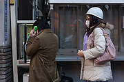 Japanese people line up to se a payphone (one wearing a protective helmet) after a magnitude .9 earthquake hit the Tohoku region of north east Japan causing tremors in Tokyo that stopped the train and cellphone networks. Many people were stranded in the centre of Tokyo over night. Tokyo, Japan Friday March 11th 2011