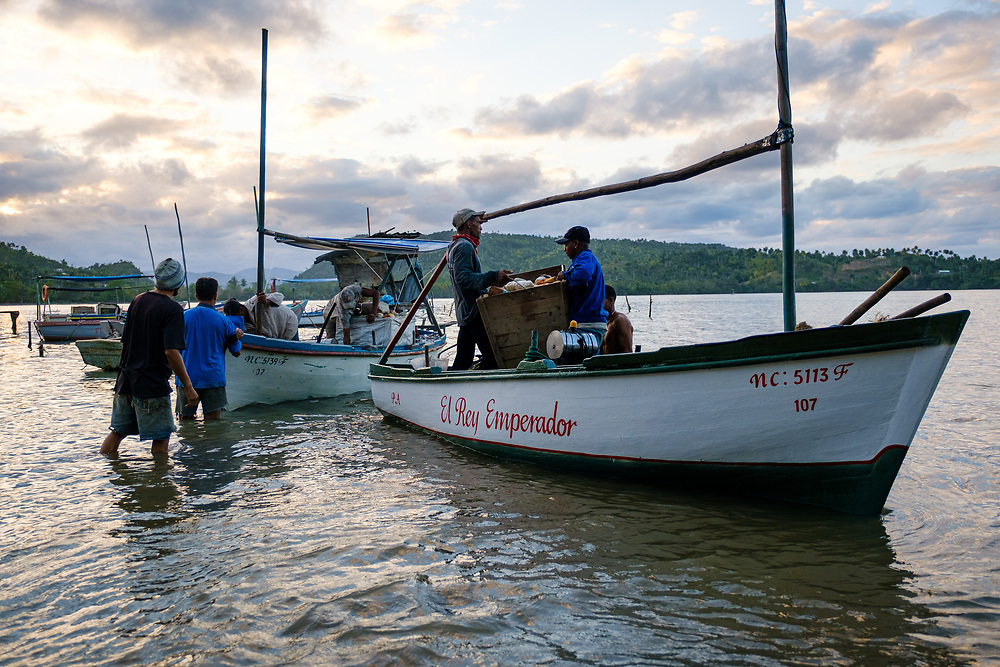 BARACOA, CUBA - CIRCA JANUARY 2020: Group of fisherman returning to Bahia de Mata, a hamlet close to Baracoa in Cuba.