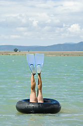 man wearing flippers with legs in the air while in an inner tube underwater