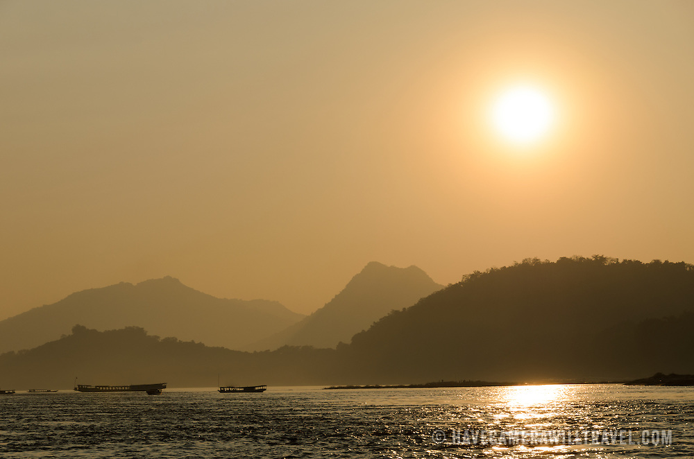 Sunset on the Mekong River near Luang Prabang in central Laos, with moutnains and boats silhouetted.