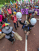 """Protestors dressed as a clown circus march towards Trafalgar Square during an Extinction Rebellion protest called """"Corruption Carnival"""" in Westminster, central London on Wednesday, Sept 3, 2020. The environmental campaign group has planned events to be held at several landmarks in the capital. Extinction Rebellion plans to hold 10 days of demonstrations across central London as part of its ongoing campaign to highlight climate change. Environmental nonviolent activists group Extinction Rebellion enters its 3rd day of continuous ten days to disrupt political institutions throughout peaceful actions swarming central London into a standoff, demanding that the central government obeys and delivers Climate and Ecological Emergency Bill and prepare for crisis with a National Citizens' Assembly. (VXP Photo/ Vudi Xhymshiti)"""