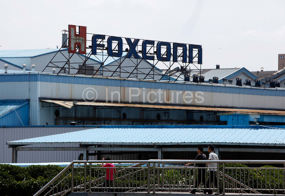 Workers walk outside Hon Hai Group's Foxconn plant in Shenzhen, China, on Wednesday, May 26, 2010. Hon Hai is the parts supplier for many hi-tech companies around the world including Apple Inc., Hewlett-Packard Co. and Dell Inc. There have been 12 suicides at the company's 300 thousand employee strong factory complex in Shenzhen so far this year. Foxconn has since moved some of its operations further inland to be closer to labor pool as well as cut costs.