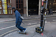 Skateboarder passing traffic survey attached to a lamppost. London, UK.