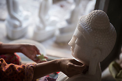Myanmar, Mandalay, woman's hands carving marble Buddha