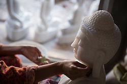 Myanmar, Mandalay, woman's hands carving marble Buddha
