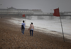 © Licensed to London News Pictures. 30/07/2021. Brighton, UK. People walk on Brighton beach in windy conditions. Parts of the south are feeling the effects of Storm Evert, the first named storm of summer 2021. Photo credit: Peter Macdiarmid/LNP