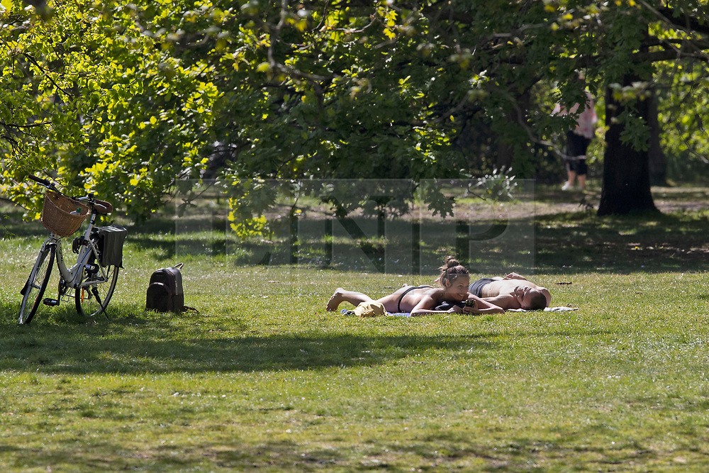 © Licensed to London News Pictures. 22/04/2020. London, UK. Members of the public sunbathe in Greenwich Park. Temperatures are set to rise throughout the rest of the week. Photo credit: George Cracknell Wright/LNP