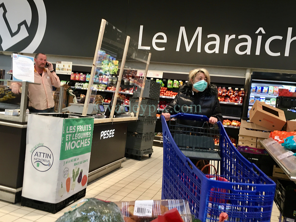 23 March 2020. Montreuil Sur Mer, Pas de Calais, France. <br /> Coronavirus - COVID-19 in Northern France.<br /> <br /> A woman wearing a face mask to help protect herself from coronavirus infection fills her shopping trolley at Leclerc supermarket in Attin near Montreuil Sur Mer. Numbers entering the store at any one time are restricted to try and maintain 'social distancing,' in an effort to halt the spread of the virus. Anyone leaving their home must carry with them an 'attestation,' in a effect a self administered permit to allow them out of the house. If stopped by the police, one must produce a valid permit along with identification papers. Failure to do so is punishable with heavy fines. Movement in France has been heavily restricted by the government.<br /> <br /> Montreuil Sur Mer was the headquarters of the British Army under Field-Marshal Sir Douglas Haig from March 1916 to April 1919. Over 1,200 year old, the ancient fortified  town with its high ramparts has endured through history, surviving the plague and King Henry VIII's invasion of France in 1544 when the Duke of Norfolk under Henry VIII's command laid a disastrous siege to the town which held firm until Norfolk was forced to withdraw in 1545. Residents are confident the ancient town can survive the coronavirus too. <br /> Photo©; Charlie Varley/varleypix.com