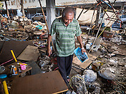 05 JANUARY 2016 - BANGKOK, THAILAND:          A man walks through the closed Bang Chak Market looking for anything that can be saved or recycled. The market closed permanently on January 4, 2016. The Bang Chak Market served the community around Sois 91-97 on Sukhumvit Road in the Bangkok suburbs. Bangkok city authorities put up notices in late November that the market would be closed by January 1, 2016 and redevelopment would start shortly after that. Market vendors said condominiums are being built on the land.                   PHOTO BY JACK KURTZ