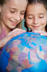 Close up of two young girls touching and spinning  a world globe