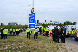 © Licensed to London News Pictures. 13/09/2021. Staines, UK. Police officers surround a protester on Poyle Interchange as protester's from climate campaign 'Insulate Britain', an offshoot of Extinction Rebellion (XR), block the clockwise slip road at Poyle Interchange/junction 14, M25 London Orbital Motorway. Photo credit: Peter Manning/LNP