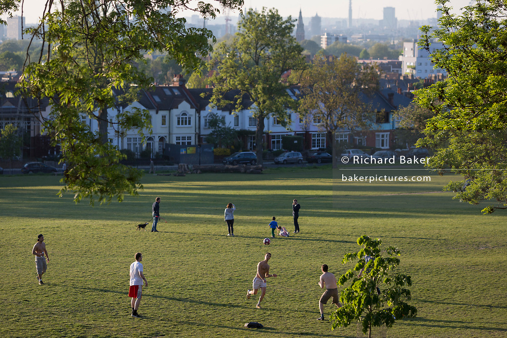 On the day that Coronavirus deaths passed the 20,000 mark in the UK, and during the continuing pandemic lockdown, a group of young men kick a ball about on the grass in early evening sunshine in Ruskin Park, a public green space in Lambeth, south London, on 25th April 2020, in London, England.