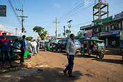 Busy street scene in Cox Bazar, Chittagong Division, Bangladesh, Asia. An Asian man walks across the road in front of a long queue of traffic including vans, CNG rickshaws and other vehicles. Other men stand around parked rickshaws.