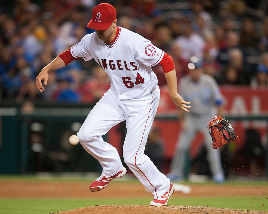 The Angels' Mike Morin drops his glove as he fields a come backer from the Royals Lorenzo Cain to end the top of the seventh inning Tuesday night at Angel Stadium.<br /> <br /> ///ADDITIONAL INFO:   <br /> <br /> angels.0427.kjs-pre  ---  Photo by KEVIN SULLIVAN / Orange County Register  --  4/26/16<br /> <br /> The Los Angeles Angels take on the Kansas City Royals Tuesday at Angel Stadium.<br /> <br /> <br />  4/26/16