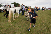 Young travellers try out a Shetland pony at the ancient annual Priddy Sheep (and horse) fair in Somerset, England. Leading round the horse on a rope, the traveller boys parade around a field on the outskirts of the village. Set in the Mendip Hills, in the south-western English county of Somerset, the Priddy Sheep fair is host to an odd mix of farmers and travellers (commonly and incorrectly known as gypsies). In this field set aside purely for travellers, many with West Country accents but also with nearby Welsh and Irish too, deals are done with a traditional spit on the hand and a smacking of palms, selling a pony to another family. The Priddy Sheep Fair moved from the city of Wells in 1348 because of the Black Death.