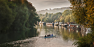 It is a hazy autumn morning. Members of the rowing club stroke their way towards Bougival from Marly on the Seine River in France  Aspect Ratio 1w x 0.5h.
