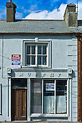 Rundown Murphy shop with estate agent for sale boards in, Kilkee, County Clare, West of Ireland