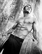 Sapeur pompier portant des tuyaux devant un vieux mur. Photographie en noir et blanc.
