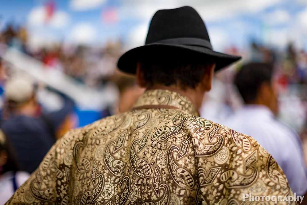 Mongolian man in traditional gold and black robe waits in the crowed of Naadam celebration