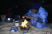 A nomad makes a fire in the Sahara desert between the cities of Chinguetti and Choum in Mauritania. Nomads live by trading their camels and produce that they buy and sell.