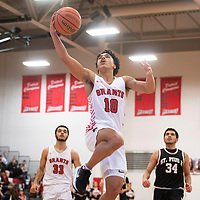 Grants Pirate Isaiah Johnson (10) drives to the basket for a layup against St. Pius X Sartans Saturday at Grants High School in Grants. Grants took the win 60-52.