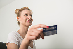 Receptionist holding a insurance card and smiling, Munich, Bavaria, Germany