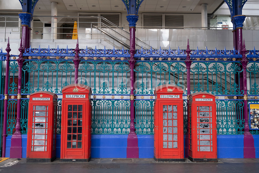 Four red telephone boxes of different sizes situated under cover in Smithfields meat market on 16th July 2020 in London, United Kingdom. This iconic design is now just an object as telecomunication via mobile phone has made the public call box obsolete.