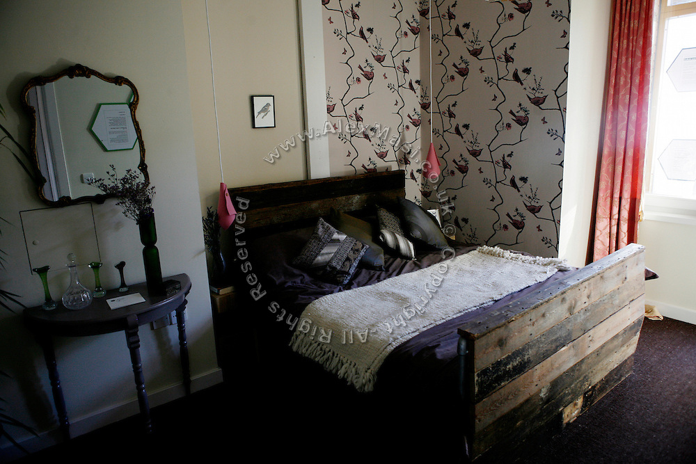 A bedroom is shown as part of an exhibition in the BedZED housing complex on Thursday, Sep. 6, 2007, in London, UK. BedZED or the Beddington Zero Energy Development, is an environmentally-friendly housing development near Wallington, England in the London Borough of Sutton. It was designed by the architect Bill Dunster who was looking for a more sustainable way of building housing in urban areas in partnership between the BioRegional Development Group and the Peabody Trust. There are 82 houses, 17 apartments and 1,405 square meters of work space were built between 2000. The project was shortlisted for the Stirling Prize in 2003. The project is designed to use only energy from renewable source generated on site. In addition to 777 square meters of solar panels, tree waste is used for heating and electricity. The houses face south to take advantage of solar gain, are triple glazed and have high thermal insulation while most rain water is collected and reused. Appliances are chosen to be water efficient and use recycled water wherever possible. Low impact building materials were selected from renewable or recycled sources and were all originating within a 35 mile radius of the site to minimize the energy required for transportation. Also, refuse collection facilities are designed to support recycling and the site encourage eco-friendly transport: electric and LPG cars have priority over petrol/diesel cars, and electricity is provided by parking spaces appositely built for charging electric cars.