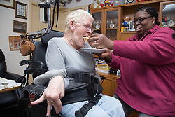 Woman with cerebral palsy being helped by a carer to eat a cake,