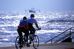 Man and woman riding a tandem bicycle along the seawall in Galveston Texas