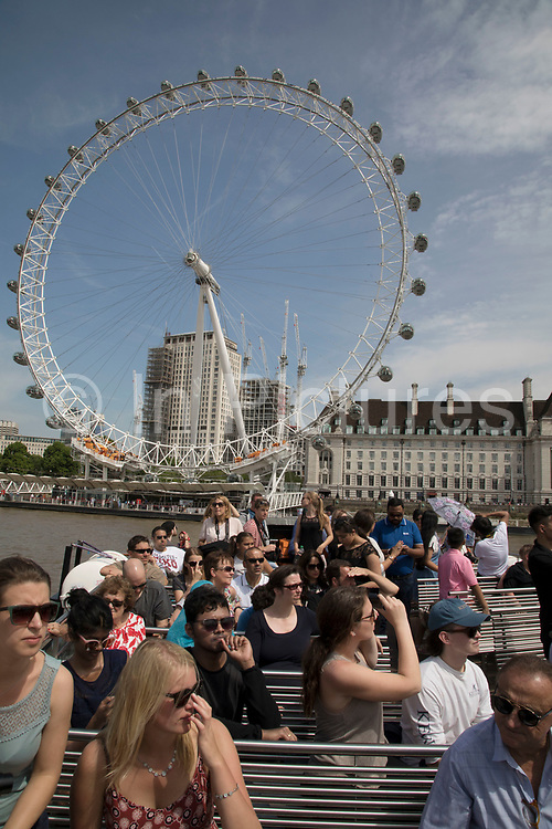 Tourists take a sightseeing tour cruise boat down the River Thames taking in some of the famous landmarks, skylines and iconic buildings in the capital, operated by City Cruises in London, England, United Kingdom. London Eye, also known as the Millennium Wheel.