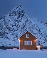 Yellow Rorbu Cabin overlooking Osltind mountain peak, Sakrisøy, Lofoten Islands, Norway