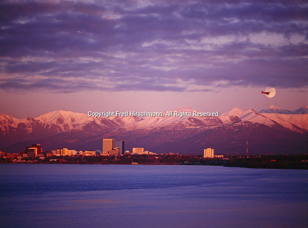 Full moon rising above the Chugach Mountains and Anchorage as bush planes fly over Cook Inlet on final approach to gravel airstrip by Lake Hood, sunset, Earthquake Park, Alaska.
